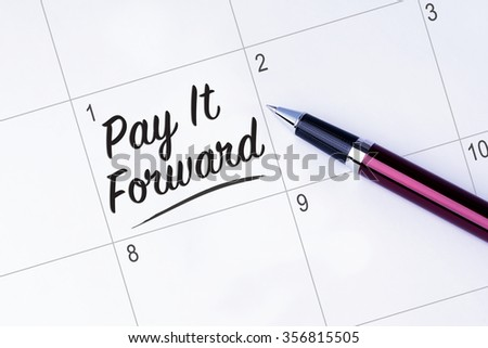The words Pay It Forward written on a calendar planner to remind you an important appointment with a pen on isolated white background. New Year concepts of goal and objective. - stock photo