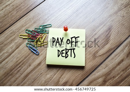 The words Pay off Debts written on a sticky note  - stock photo
