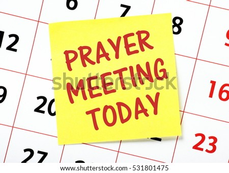 The words Prayer Meeting Today written on a yellow sticky note posted on a wall calendar as a reminder