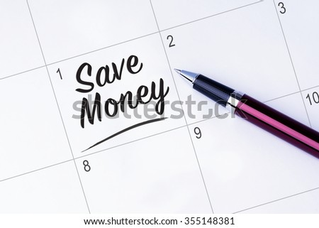 The words Save Money written on a calendar planner to remind you an important appointment with a pen on isolated white background. New Year concepts of goal and objective. - stock photo