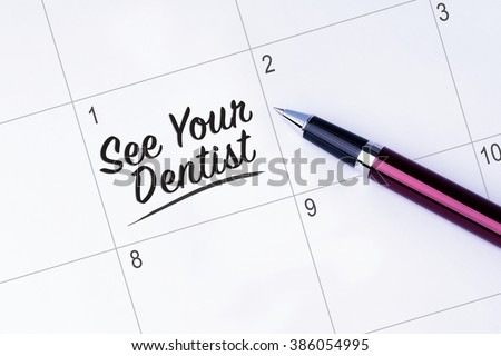 The words See Your Dentist written on a calendar planner to remind you an important appointment with a pen on isolated white background.