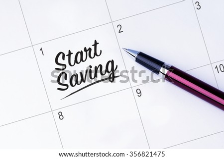 The words Start Saving written on a calendar planner to remind you an important appointment with a pen on isolated white background. New Year concepts of goal and objective. - stock photo