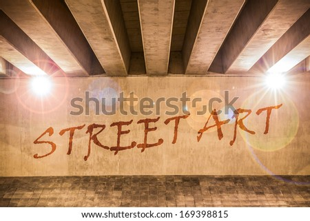 The words street art painted as graffiti on the support column of an overpass - stock photo
