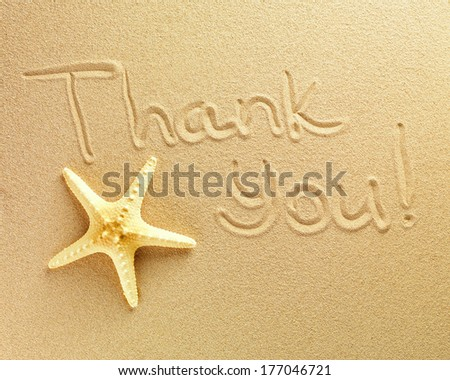 The words Thank You are written on a sand background and the starfish is lying nearby - stock photo