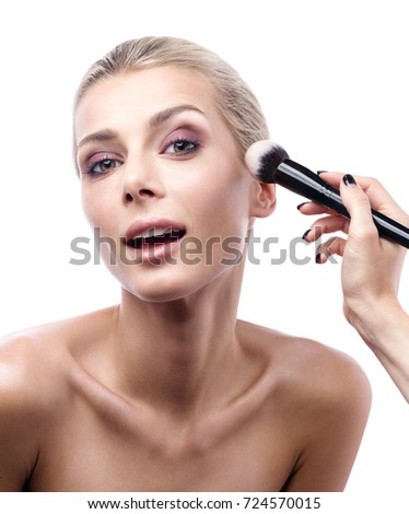 The work of a professional makeup artist. The beautiful young woman's face and brush the powder in close-up. The smile and pleasure. Beauty portrait isolated on white background.