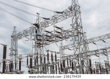 The worker at high-voltage electric substation - stock photo