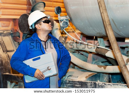 The worker dressed in overalls clothing checks up an industrial equipment - stock photo