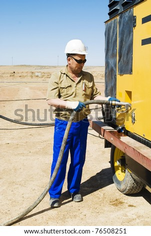 The worker fills the compressor with fuel on industrial site