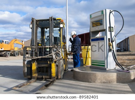 The worker fills with fuel a loader - stock photo