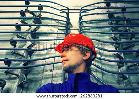 The worker in a helmet at factory.Industrial interior.Retro toning. - stock photo
