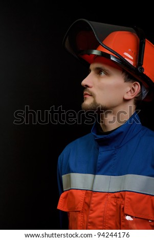 The worker in overalls and a helmet on a black background - stock photo