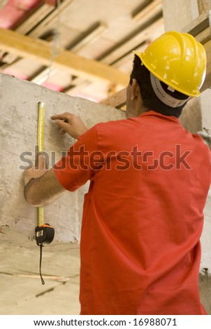 The worker is standing looking at the blueprint.  He is making measurements off of the blueprint.  Vertically framed shot.