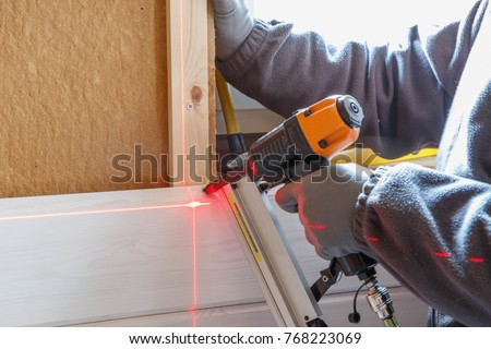 The worker makes finishing works of walls with a white wooden board, using laser line level. Building heat-insulating eco-wooden frame house with wood fiber plates