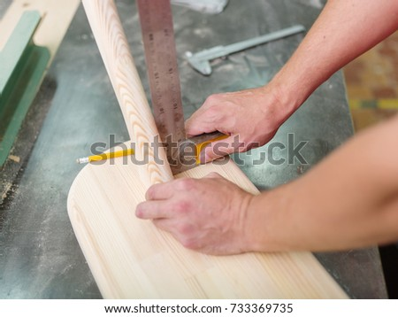 The worker marks the dimensions on his product