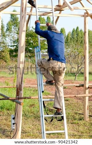 The Worker men climbing  ladder down - stock photo