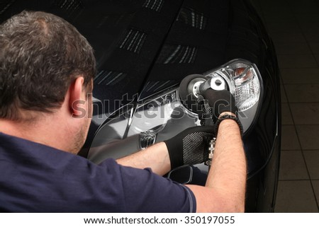 The worker polishes optics of headlights of the car with the electric tool. Close up - stock photo