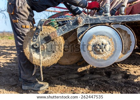 The worker repairing the tractor on the field - stock photo