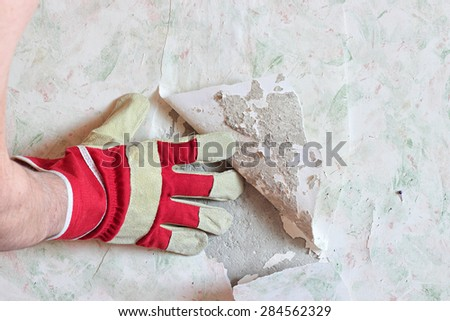 The worker's hand in a glove deletes old wallpaper from a wall.
