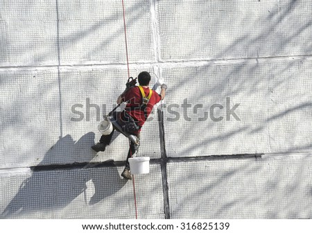 The worker seals hermetically seams of the panel house. Work at height.