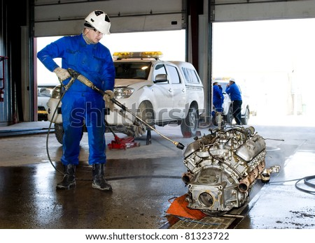 The worker washes the motor - stock photo