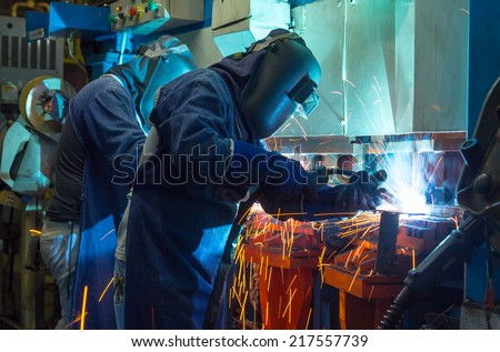 The working in Welding skill up. (Manufacturing of car) Filled with smoke around them. - stock photo