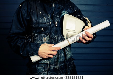 The workman holds in his hand a white protective helmet and construction drawings in Finland. The Worker's coverall is dirty. Image includes a effect. - stock photo