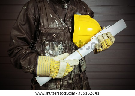 The workman holds in his hand a yellow protective helmet and construction drawings in Finland. The Worker's coverall is dirty. Image includes a effect. - stock photo