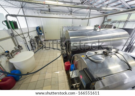 The workshop in the dairy farm with chrome tanks for milk - stock photo