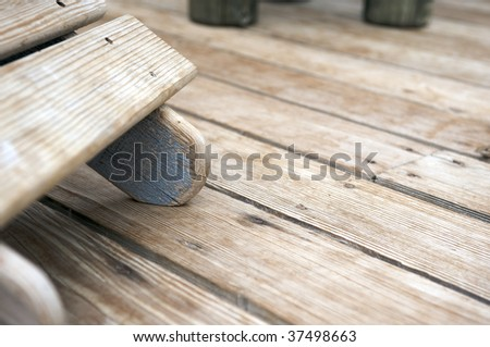 The worn foot of a comfortable sun lounger on a wooden deck bleached by the sun - stock photo
