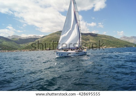 """The yacht under white sails on a background of mountains. Tivat, Montenegro - 26 April, 2016. Regatta """"Russian stream"""" in God-Katorskaya bay of the Adriatic Sea off the coast of Montenegro. - stock photo"""