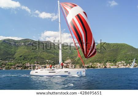 "The yacht with a multi-colored sail. Tivat, Montenegro - 26 April, 2016. Regatta ""Russian stream"" in God-Katorskaya bay of the Adriatic Sea off the coast of Montenegro. - stock photo"