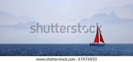 The yacht with a red sail on a mountain background in the red sea