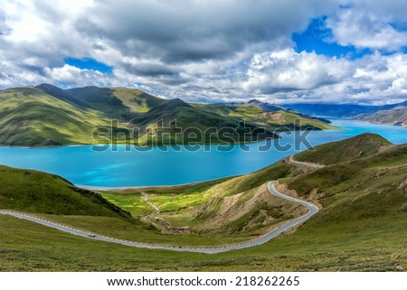 The Yamdrok Lake under the sunny blue sky in Tibet of China. - stock photo