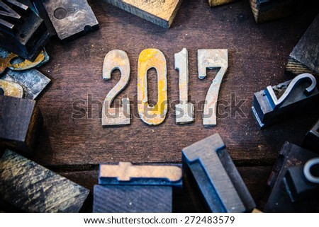 The year 2017 written in rusted metal letters surrounded by vintage wooden and metal letterpress type. - stock photo