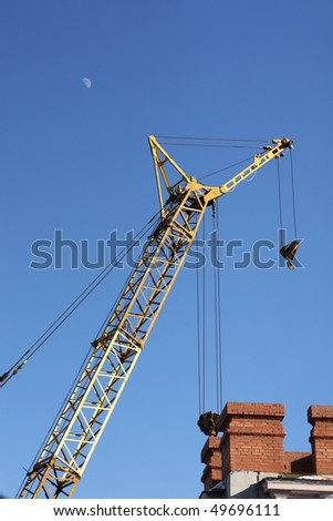 The yellow crane and red brick building under the moon in the blue sky vertical - stock photo