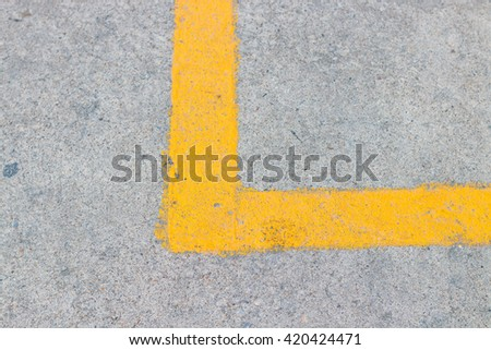 The yellow line on the cement floor.