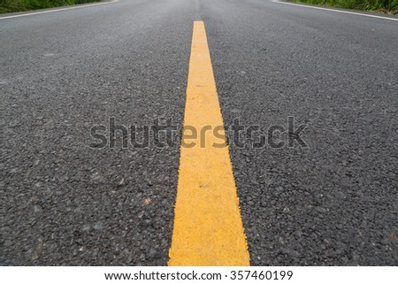 The yellow line on the road with tree and sky background