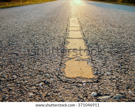 The yellow line on the road with tree and sky background. - stock photo