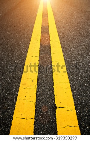 The yellow traffic lines on the road with sunlight. - stock photo