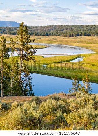 The Yellowstone River flows through he Heyden Valley before going over the Falls of the Yellowstone. - stock photo