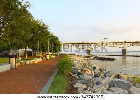 The Yorktown Riverwalk and waterfront beach area during early morning sunrise looking west towards Williamsburg through the Coleman bridge as the sun rises in the east - stock photo