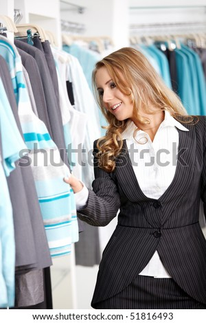 The young attractive girl considers clothes in shop - stock photo