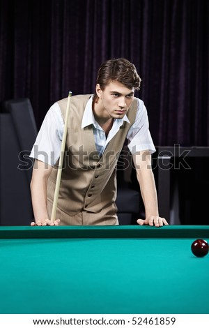 The young attractive man plays billiards - stock photo
