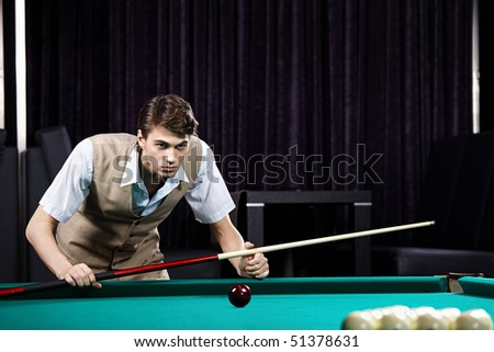 The young attractive well dressed man plays billiards - stock photo