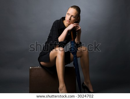 the young attractive woman assidenous on retro suitcase