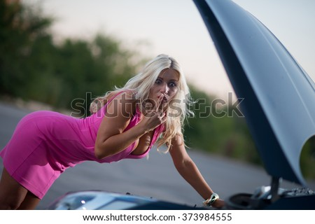 the young attractive woman's car broke down on the road - stock photo