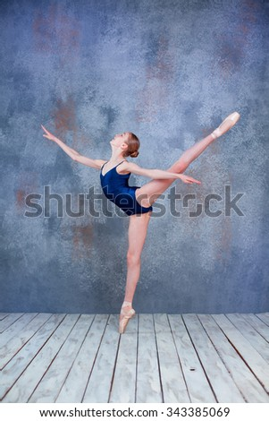 The  young ballerina  posing in studio on gray background - stock photo