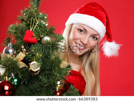 The young beautiful girl dressed as Santa and a christmas fur-tree - stock photo