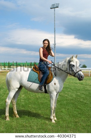 The young beautiful girl embraces a white horse - stock photo