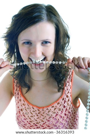 The young beautiful girl holds a pearl beads, showing a whiteness of the teeth. Isolation on a white background